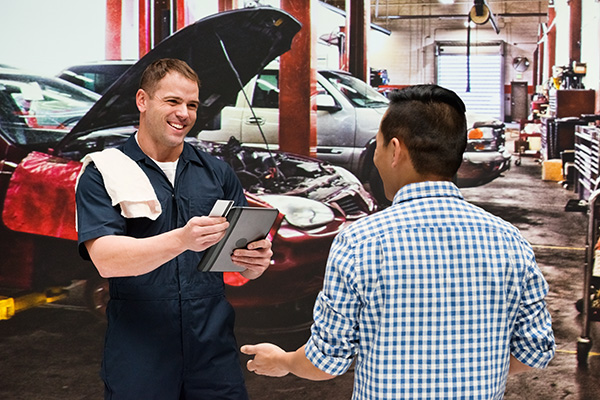 Mechanic discussion with client in auto repair shop